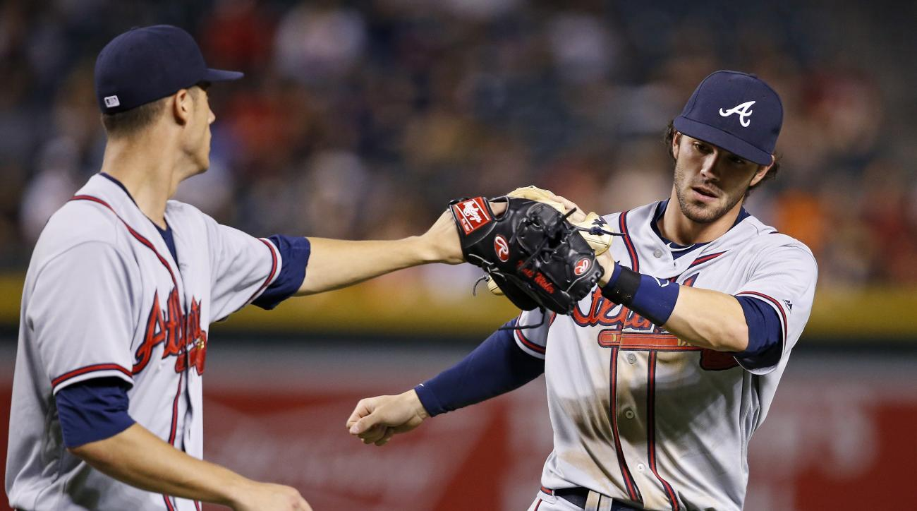 Atlanta Braves' Matt Wisler, left, slaps gloves with Dansby Swanson, right, after Swanson made a long throw from deep shortstop to get Arizona Diamondbacks' Mitch Haniger out at first base during the fourth inning of a baseball game Thursday, Aug. 25, 201