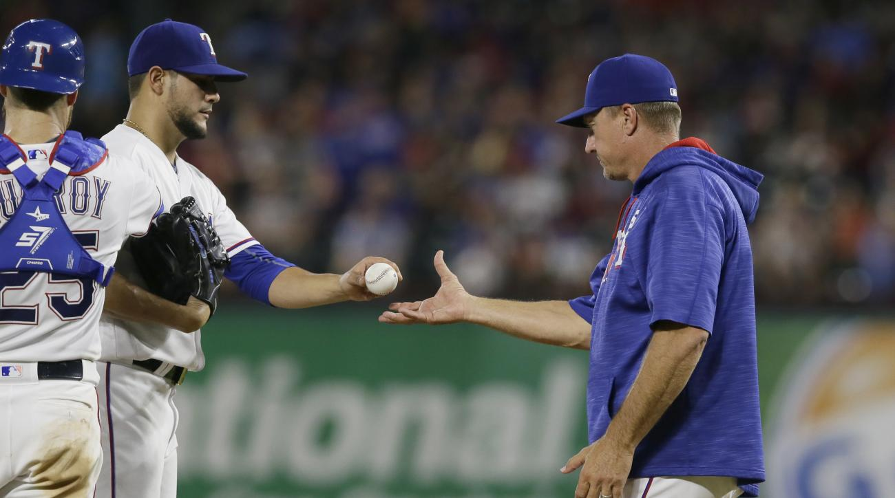 Texas Rangers manager Jeff Banister, right, pulls starting pitcher Martin Perez from the baseball game as catcher Jonathan Lucroy (25) stands by during the sixth inning against the Cleveland Indians in Arlington, Texas, Friday, Aug. 26, 2016. (AP Photo/LM