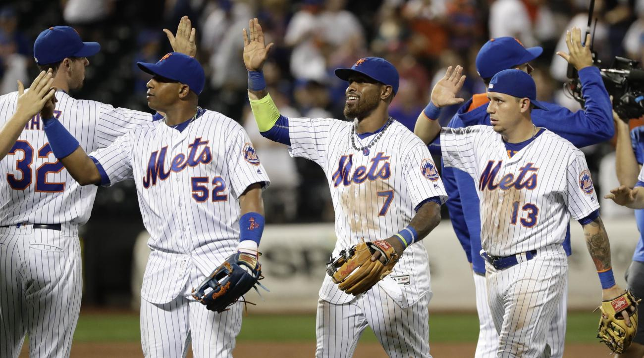 New York Mets' Yoenis Cespedes (52), Jose Reyes (7) and Asdrubal Cabrera (13) celebrate with teammates after a baseball game against the Philadelphia Phillies on Friday, Aug. 26, 2016, in New York. The Mets won 9-4. (AP Photo/Frank Franklin II)