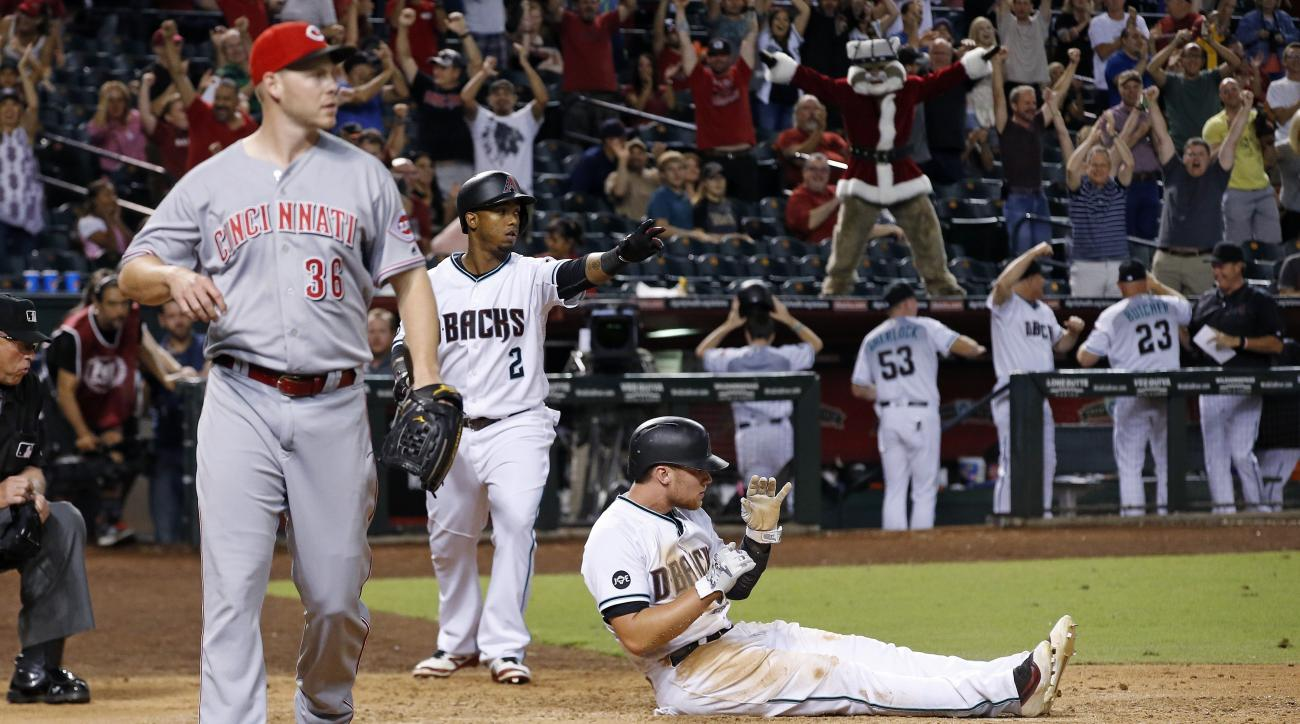 Arizona Diamondbacks' Brandon Drury, right, sits near home plate after scoring the winning run on a wild pitch by Cincinnati Reds' Blake Wood, left, as Diamondbacks' Jean Segura (2) watches during the 11th inning of a baseball game Friday, Aug. 26, 2016,