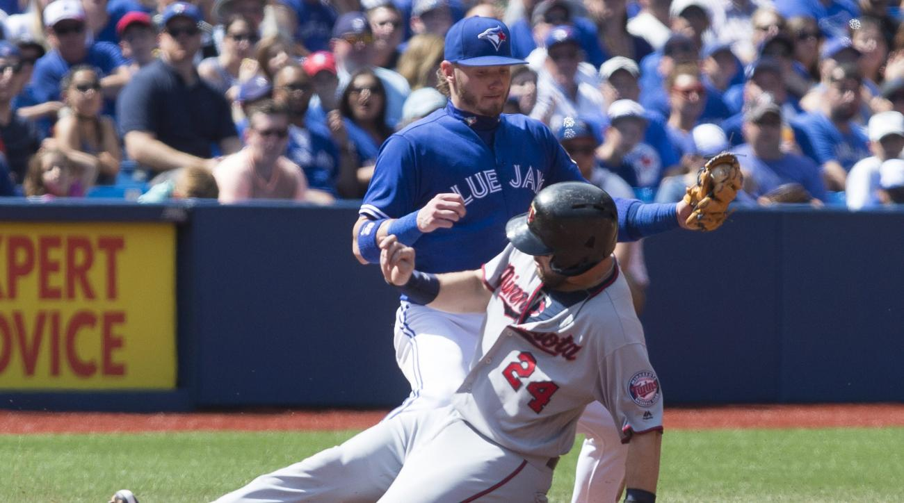 Minnesota Twins' Trevor Plouffe (24) slides safely into third base in front of Toronto Blue Jays' Josh Donaldson during the fourth inning of a baseball game in Toronto, Saturday, Aug. 27, 2016, 2016. (Chris Young/The Canadian Press via AP)