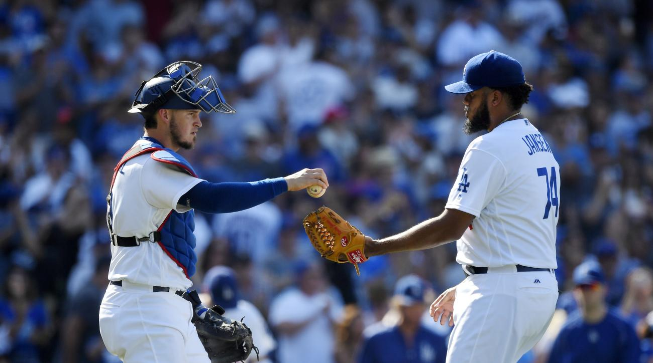 Los Angeles Dodgers catcher Yasmani Grandal, left, gives relief pitcher Kenley Jansen the ball after the Dodgers defeated the Chicago Cubs 3-2 in a baseball game, Saturday, Aug. 27, 2016, in Los Angeles. (AP Photo/Mark J. Terrill)