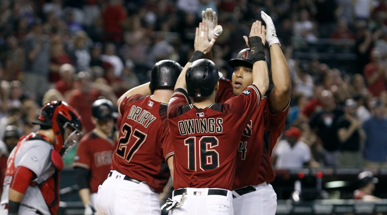 Arizona Diamondbacks' Yasmany Tomas, right, is congratulated by teammates Brandon Drury (27) and Chris Owings as he crosses the plate following his three-run home run against the Cincinnati Reds during the sixth inning of a baseball game, Sunday, Aug. 28,