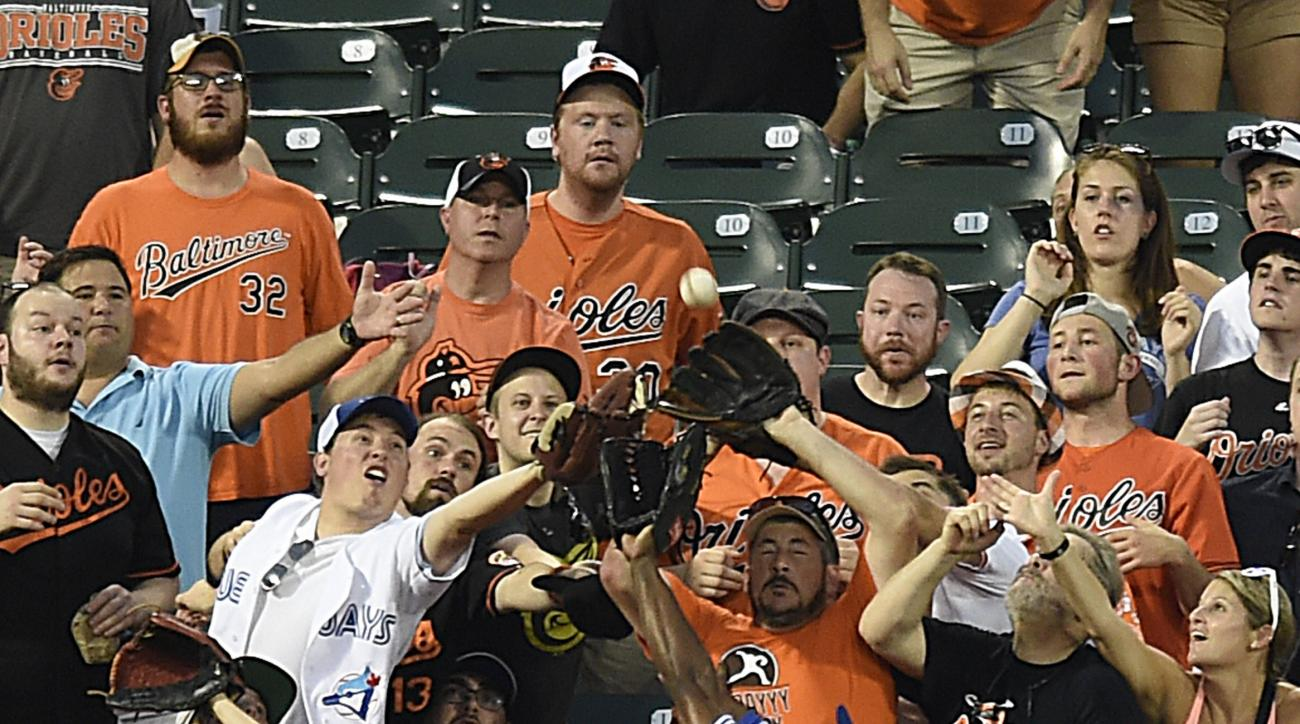 Toronto Blue Jays left fielder Melvin Upton reaches into the crowd but is unable to catch a solo home run by Baltimore Orioles' J.J. Hardy in the third inning of a baseball game, Monday, Aug. 29, 2016, in Baltimore. (AP Photo/Gail Burton)