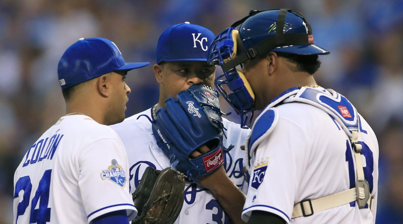 Kansas City Royals starting pitcher Edinson Volquez (36) talks with catcher Salvador Perez (13) and third baseman Christian Colon (24) during the first inning of a baseball game against the New York Yankees at Kauffman Stadium in Kansas City, Mo., Tuesday