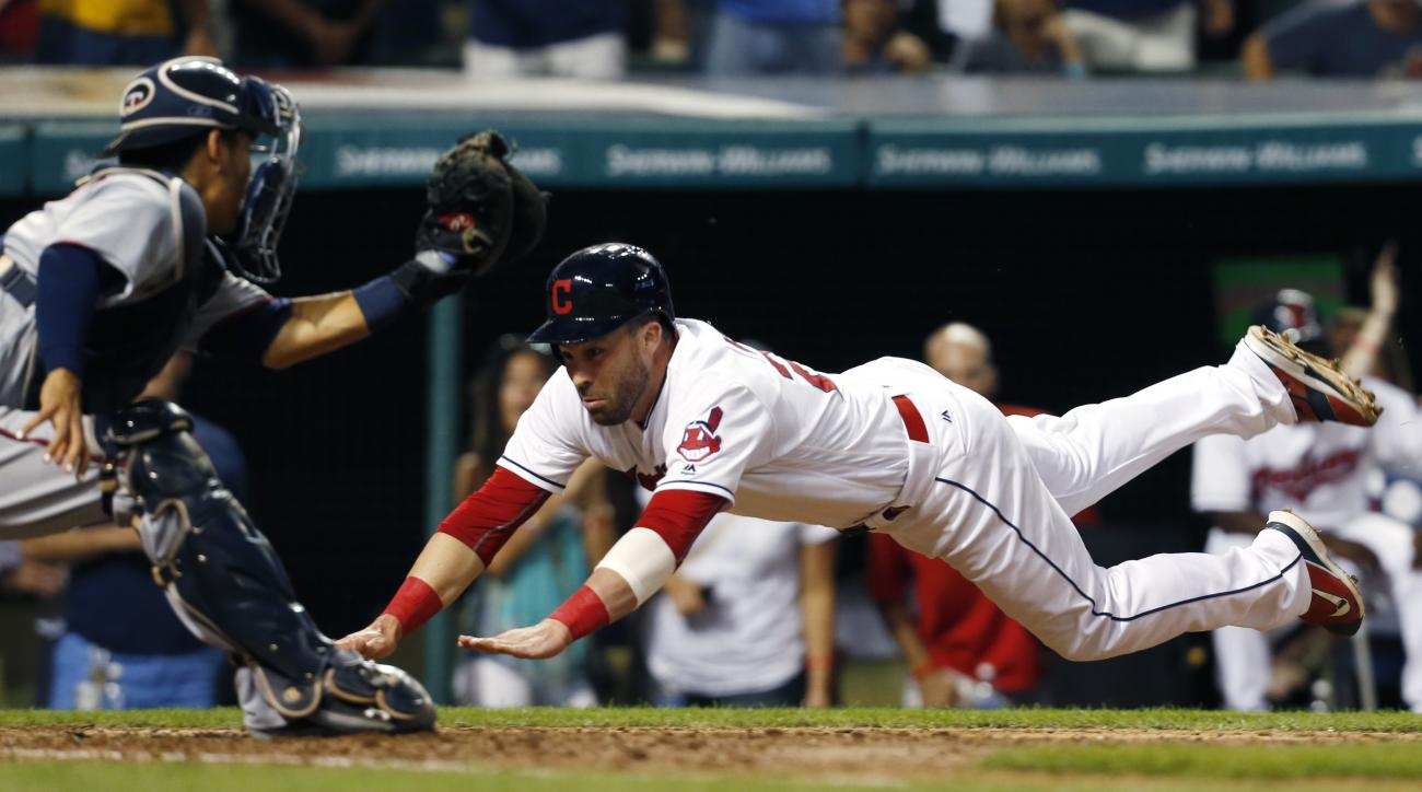Cleveland Indians' Jason Kipnis (22) dives into home plate and is tagged out by Minnesota Twins' Kurt Suzuki (8) on a ball hit by Francisco Lindor during the fourth inning of a baseball game Tuesday, Aug. 30, 2016, in Cleveland. (AP Photo/Ron Schwane)