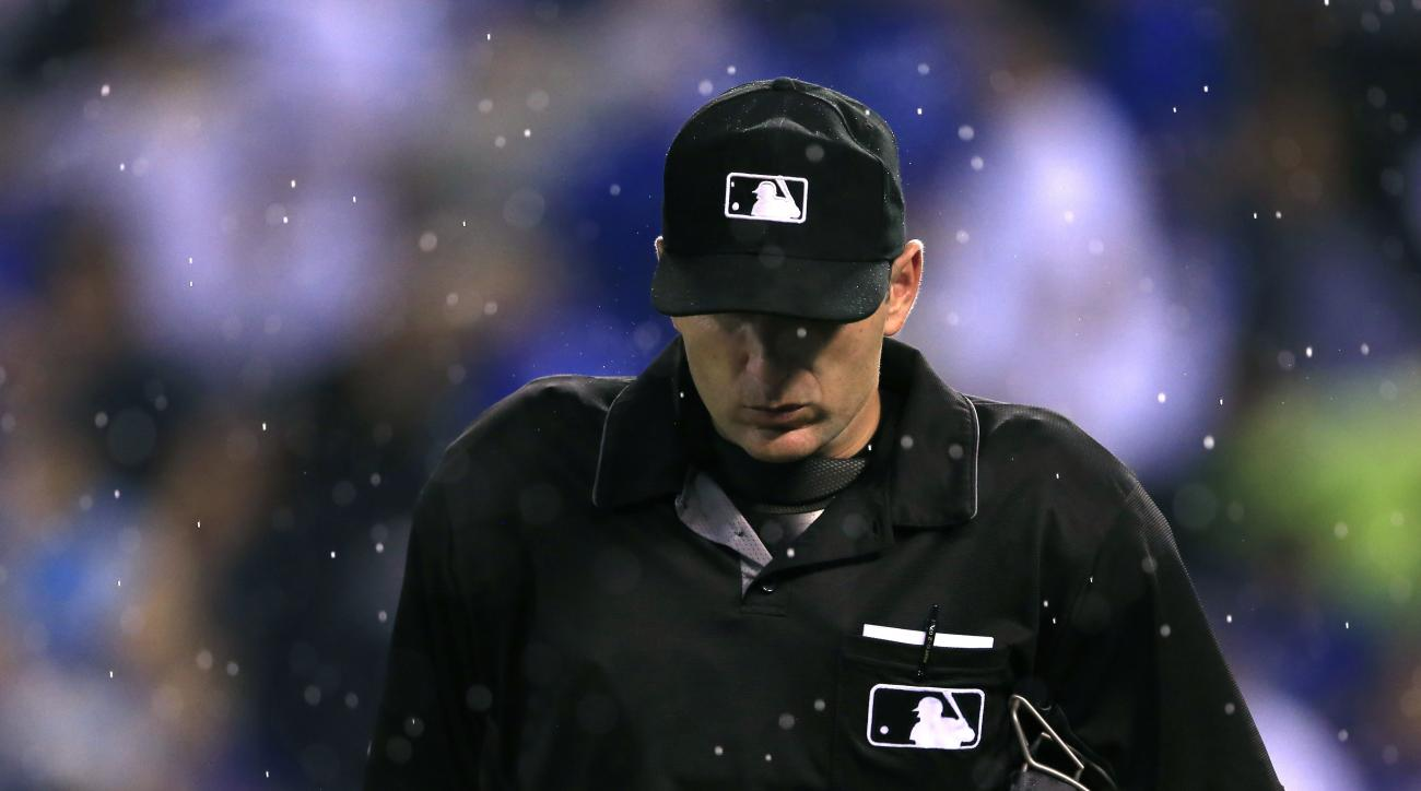 Home plate umpire Pat Hoberg walks off the field as rain begins to fall during the fifth inning of a baseball game between the Kansas City Royals and the New York Yankees at Kauffman Stadium in Kansas City, Mo., Tuesday, Aug. 30, 2016. (AP Photo/Orlin Wag