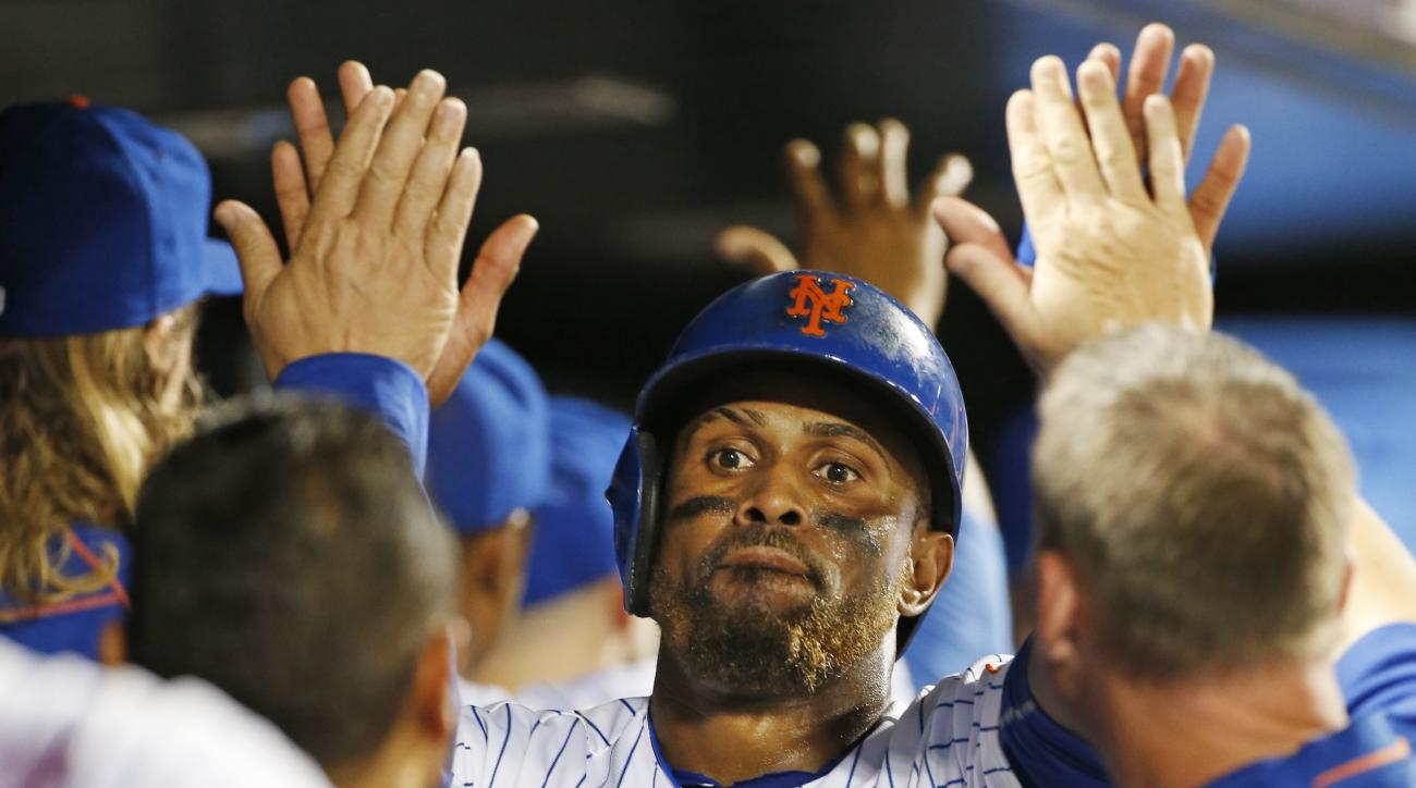 New York Mets' Jose Reyes greets teammates in the dugout after scoring on Alejandro de Aza's sixth-inning RBI single in a baseball game against the Miami Marlins, Tuesday, Aug. 30, 2016, in New York. The Mets won 7=4(AP Photo/Kathy Willens)