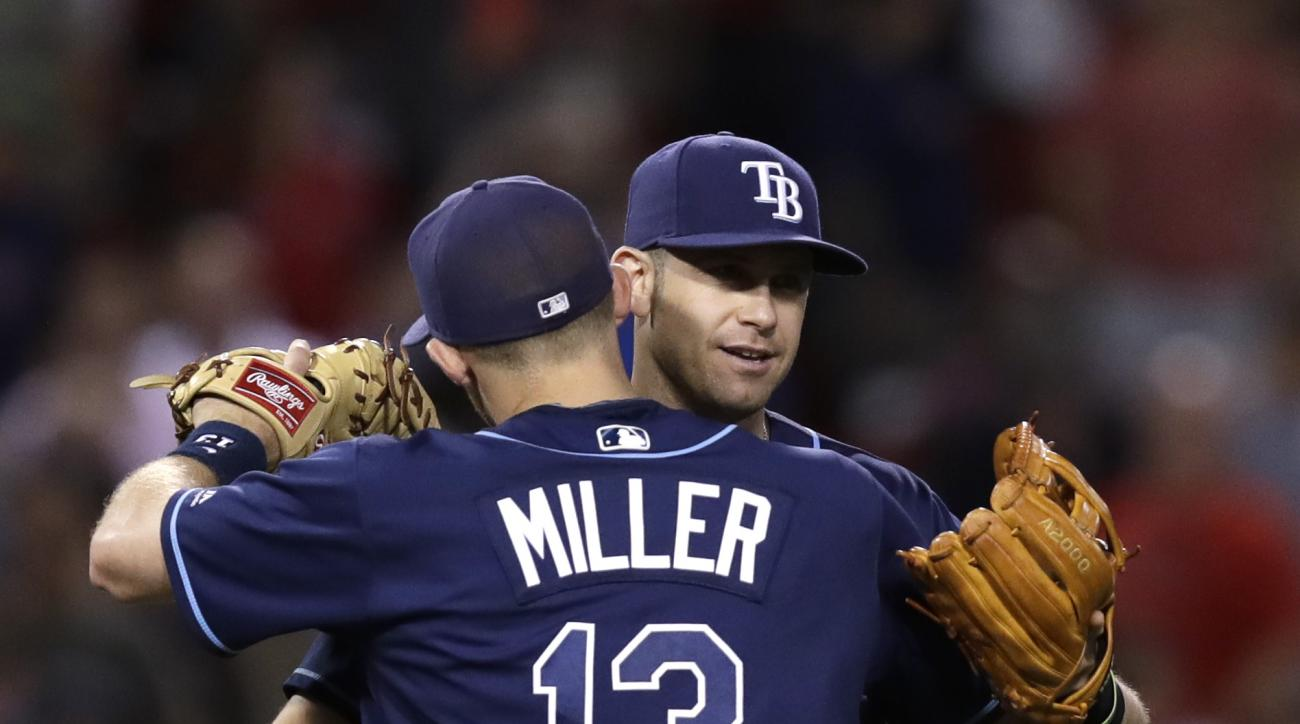 Tampa Bay Rays third baseman Evan Longoria is embraced by Brad Miller (13) after the Rays defeated the Boston Red Sox in a baseball game at Fenway Park, Tuesday, Aug. 30, 2016, in Boston. Longoria scored the go-ahead run on a home run, breaking a 3-3 tie,