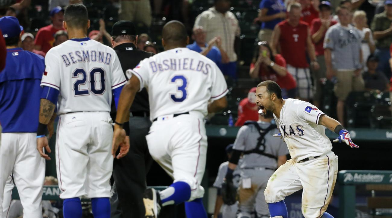 Texas Rangers' Ian Desmond (20), Delino DeShields (3) and others wait for Rougned Odor, right, at home after Odor hit a walk-off two-run home run in a baseball game against the Seattle Mariners on Tuesday, Aug. 30, 2016, in Arlington, Texas. The Rangers w