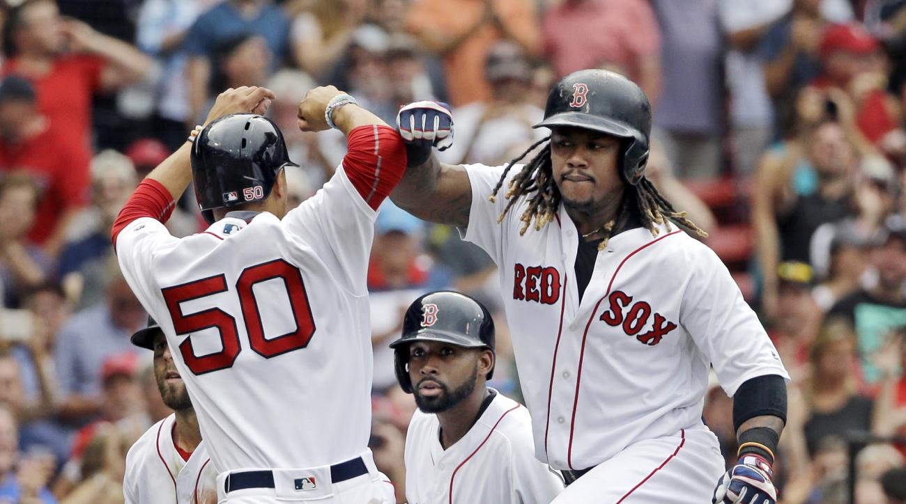Boston Red Sox's Hanley Ramirez celebrates his grand slam with Mookie Betts (50) as Jackie Bradley Jr., center, watches in the fifth inning of a baseball game against the Tampa Bay Rays at Fenway Park, Wednesday, Aug. 31, 2016, in Boston. (AP Photo/Elise