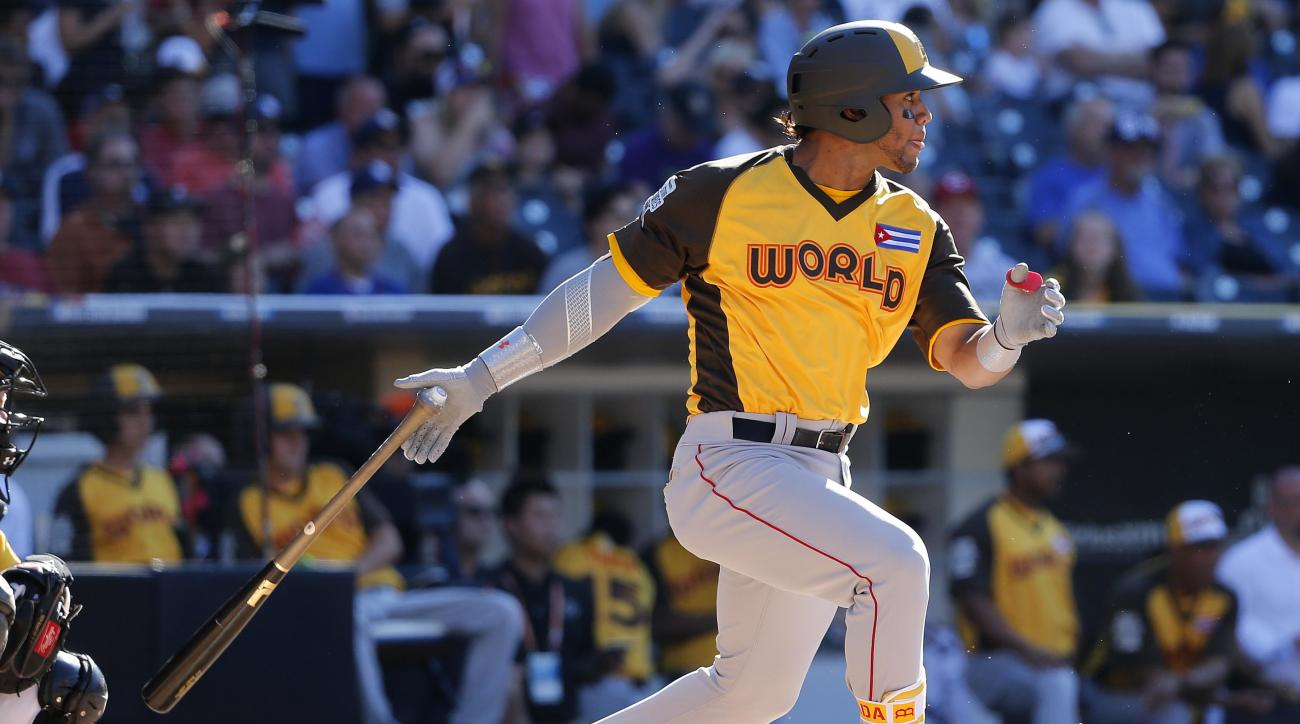 FILE - In this July 10, 2016, file photo, World team's Yoan Moncada, of the Boston Red Sox, hits against the U.S. team during the All-Star Futures baseball game in San Diego. The Red Sox will add hyped prospect Moncada to the major league roster prior to