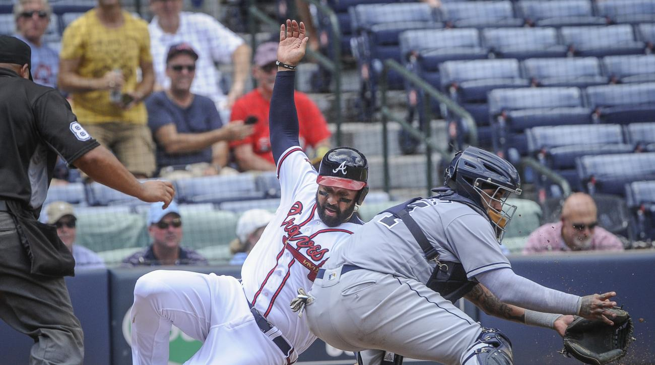 Atlanta Braves' Matt Kemp slides safely past San Diego Padres catcher Hecter Sanchez, right, to score on an Anthony Recker two run line drive single to right field during the fifth inning of a baseball game, Thursday, Sept. 1, 2016, in Atlanta. (AP Photo/