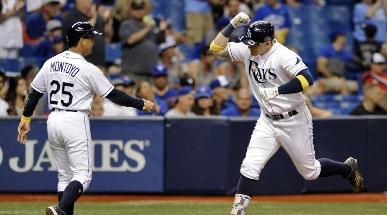 Tampa Bay Rays third base coach Charlie Montoyo, left, congratulates Logan Morrison, right, who hit a two-run home run off Toronto Blue Jays starter Marcus Stroman during the sixth inning of a baseball game Friday, Sept. 2, 2016, in St. Petersburg, Fla. (