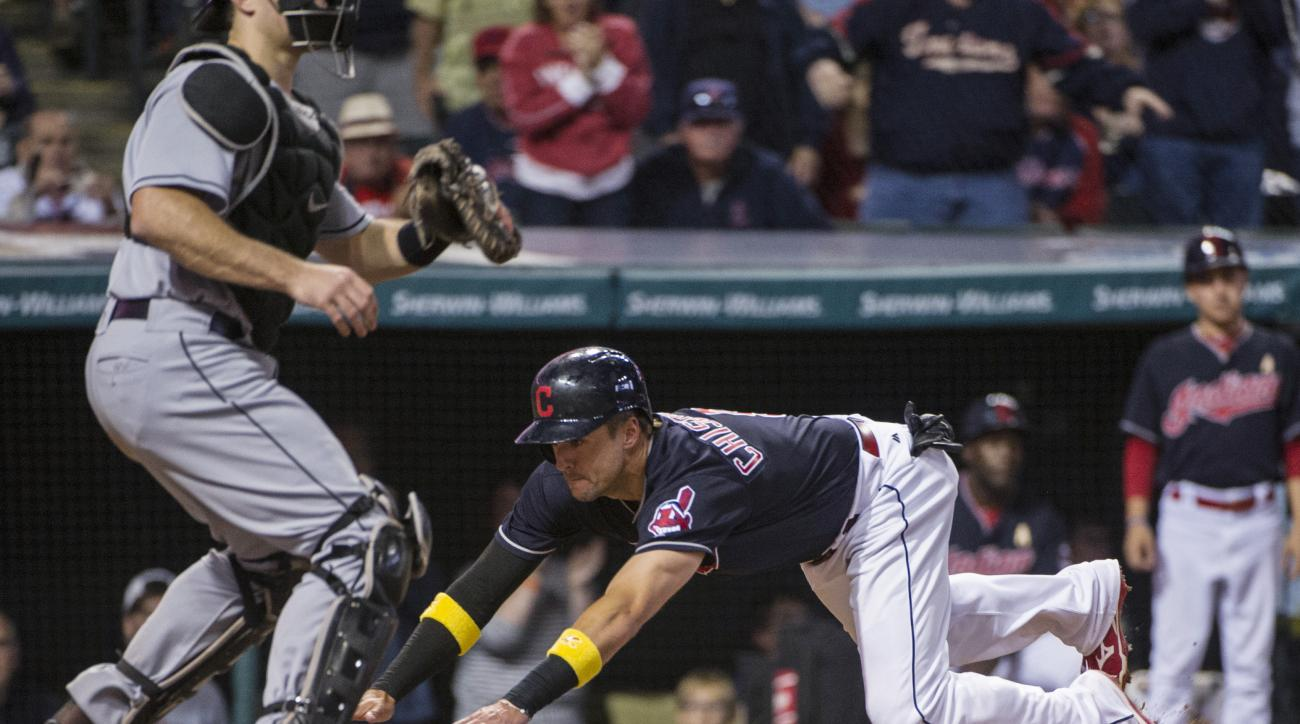 Cleveland Indians' Lonnie Chisenhall dives into home plate to score on a hit by Abraham Almonte against the Miami Marlins during the fifth inning of a baseball game in Cleveland, Friday, Sept. 2, 2016. Marlins catcher J.T. Realmuto waits for the throw. (A