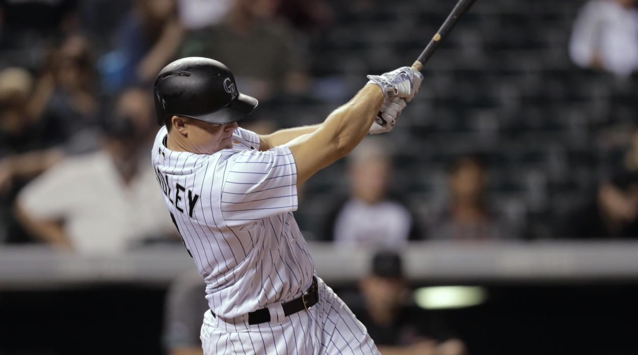 Colorado Rockies' Nick Hundley follows through on a grand slam off Arizona Diamondbacks relief pitcher Silvino Bracho during the eighth inning of a baseball game Friday, Sept. 2, 2016, in Denver. The Rockies won 14-7. (AP Photo/David Zalubowski)