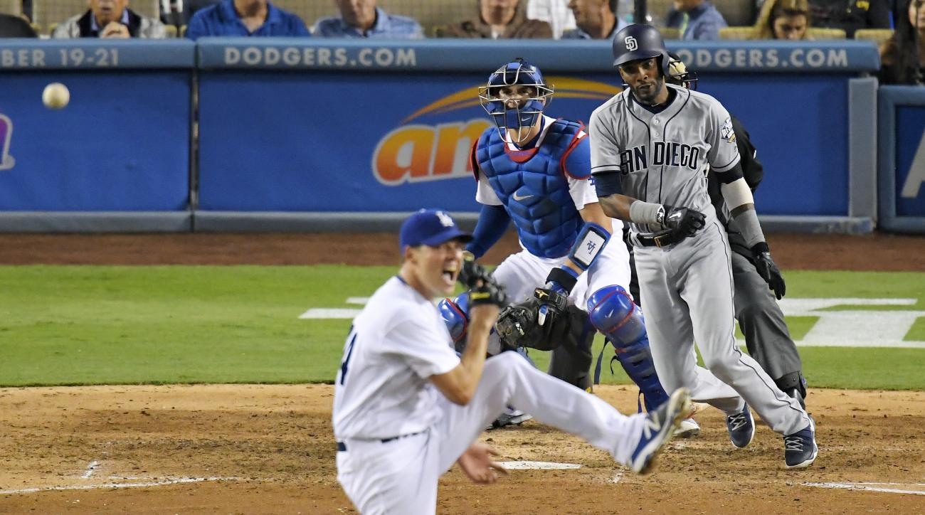 San Diego Padres' Alexei Ramirez, right, hits a single past Los Angeles Dodgers starting pitcher Rich Hill, left, as catcher Yasmani Grandal watches during the sixth inning of a baseball game, Saturday, Sept. 3, 2016, in Los Angeles. Hill had a no-hitter