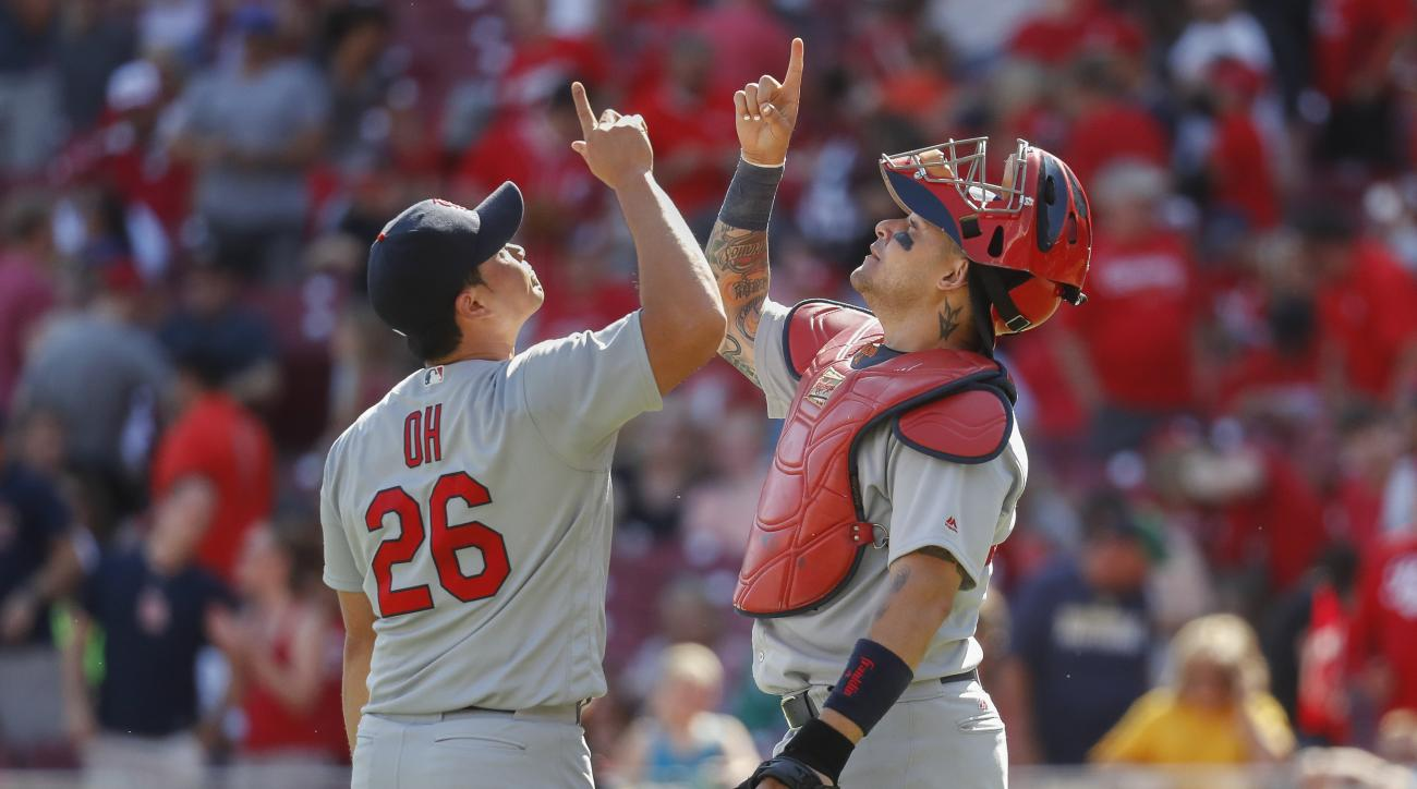 St. Louis Cardinals relief pitcher Seung Hwan Oh (26) and catcher Yadier Molina, right, celebrate after closing the ninth inning of a baseball game, against the Cincinnati Reds, Sunday, Sept. 4, 2016, in Cincinnati. (AP Photo/John Minchillo)