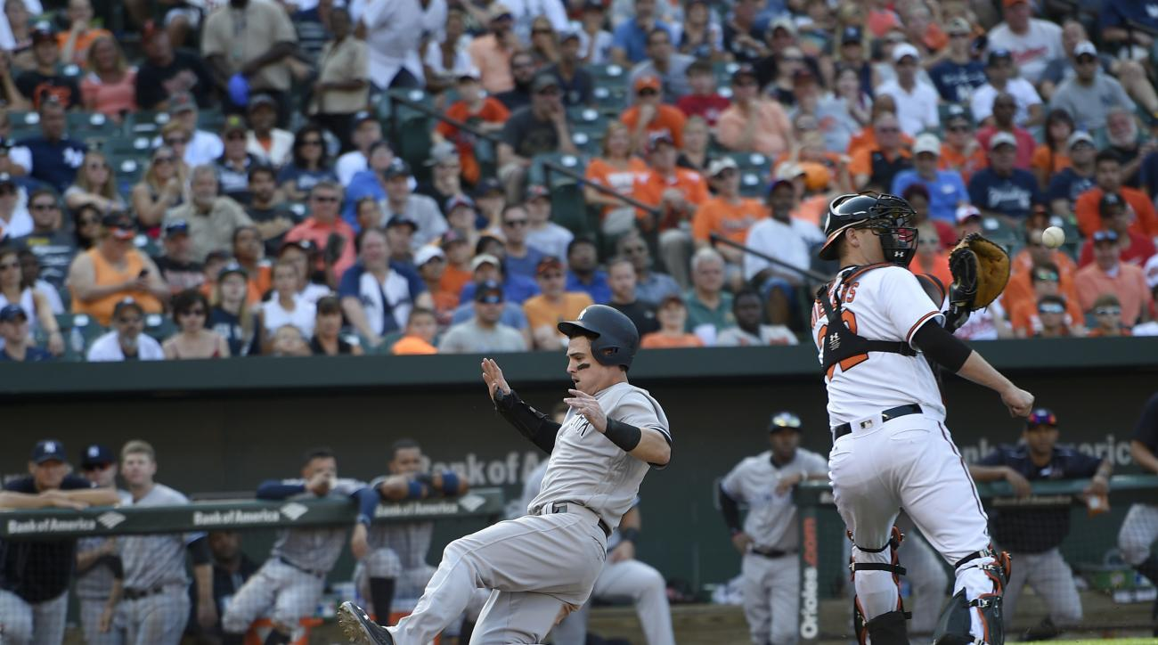 New York Yankees' Tyler Austin, left, starts his slide toward home to score as on a sacrifice fly by Brett Gardner as Baltimore Orioles catcher Matt Wieters, right, waits for the ball during the ninth inning of a baseball game, Sunday, Sept. 4, 2016, in B