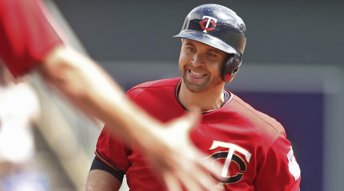 Minnesota Twins' Brian Dozier smiles as the third base coach reaches out to congratulate him as he jogs the base path on a solo home run off Kansas City Royals pitcher Ian Kennedy in the first inning of a baseball game Monday, Sept. 5, 2016, in Minneapoli