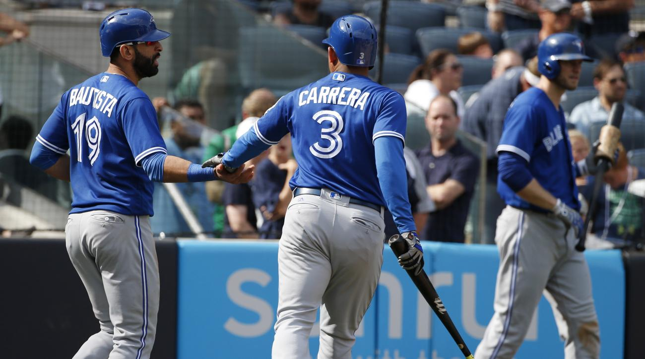 Toronto Blue Jays' Jose Bautista (19) and Ezequiel Carrera (3) celebrate after scoring on Edwin Encarnacion's two-run single during the seventh inning of a baseball game against the New York Yankees in New York, Monday, Sept. 5, 2016. (AP Photo/Kathy Will