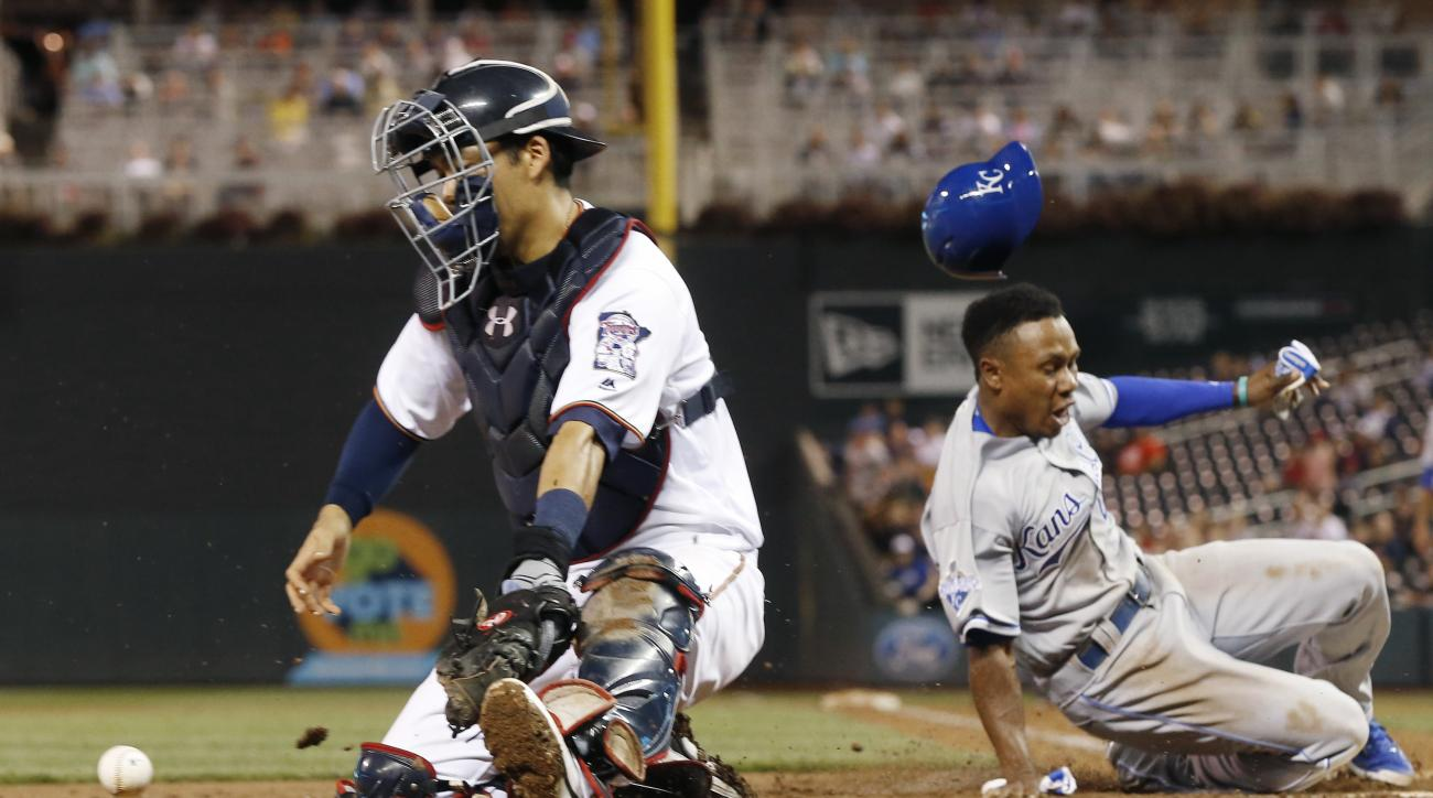 Minnesota Twins catcher Kurt Suzuki, left, chases the wide throw from left as Kansas City Royals pinch-runner Terrence Gore scores on a single by Alcides Escobar during the seventh inning of a baseball game Tuesday, Sept. 6, 2016, in Minneapolis. (AP Phot