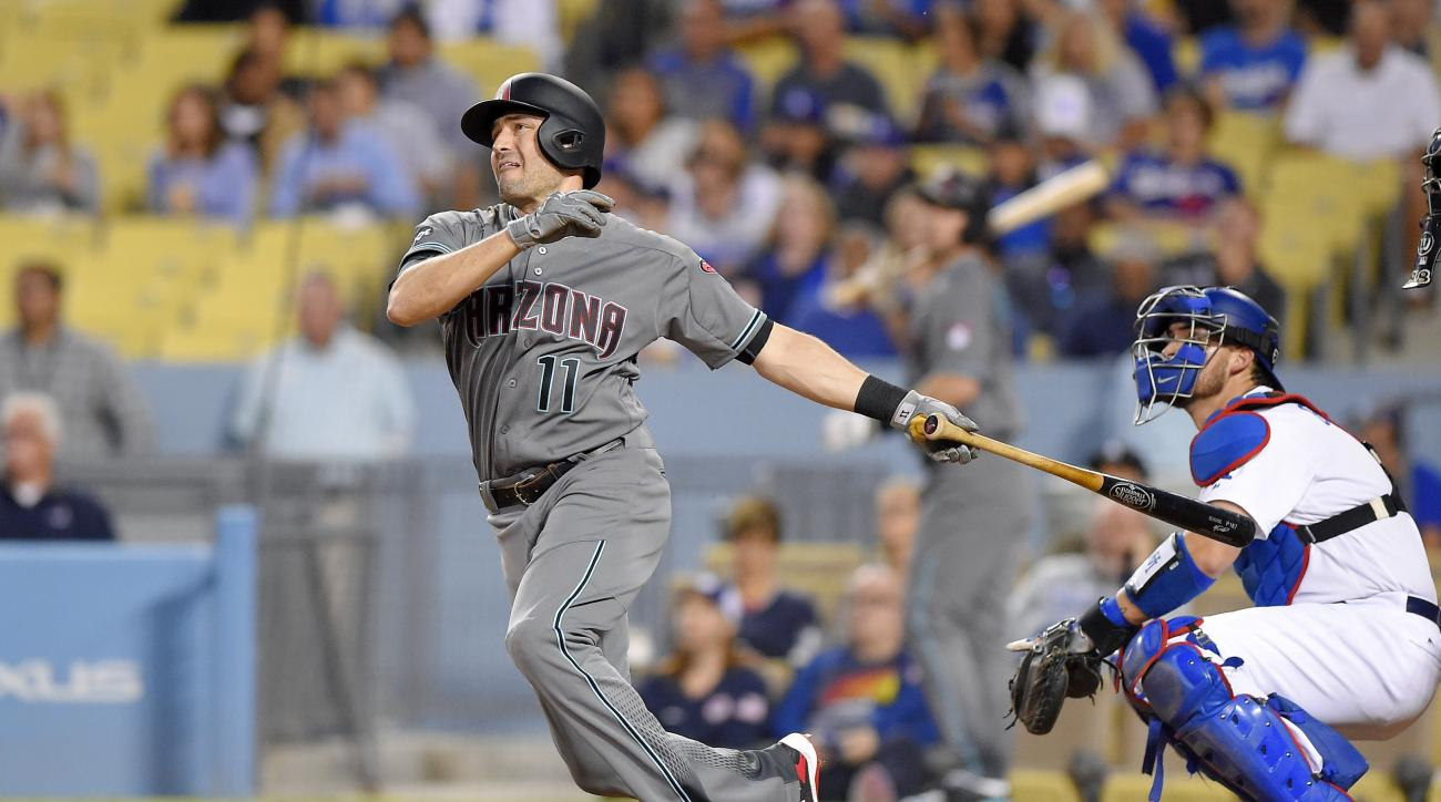 Arizona Diamondbacks' A.J. Pollock, left, hits a solo home run as Los Angeles Dodgers catcher Yasmani Grandal watches during the first inning of a baseball game, Tuesday, Sept. 6, 2016, in Los Angeles. (AP Photo/Mark J. Terrill)