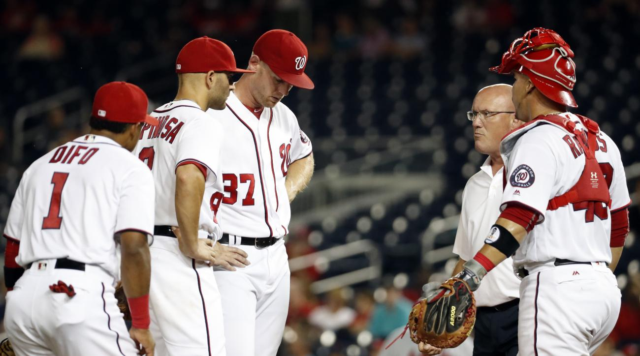 CORRECTS DIFO'S POSITION TO THIRD BASEMAN, NOT SHORTSTOP - Washington Nationals third baseman Wilmer Difo, left, and shortstop Danny Espinosa, stand as starting pitcher Stephen Strasburg is approached by trainer Paul Lessard, with catcher Wilson Ramos, du