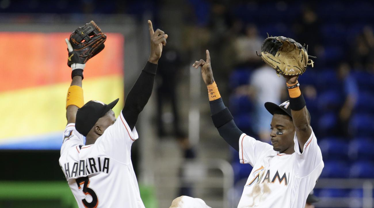Miami Marlins shortstop Adeiny Hechavarria (3) and second baseman Dee Gordon, right, celebrate the Marlins' 6-0 win over the Philadelphia Phillies in a baseball game, Wednesday, Sept. 7, 2016, in Miami. (AP Photo/Lynne Sladky)