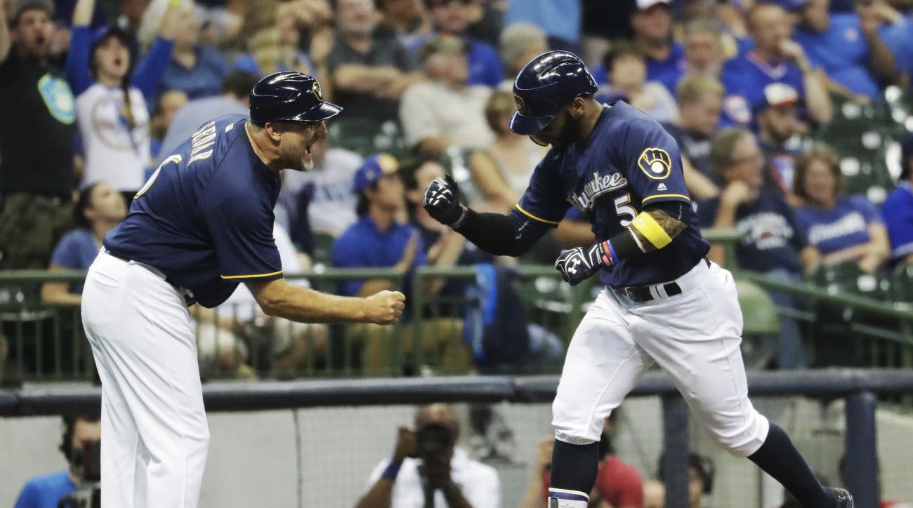 Milwaukee Brewers' Jonathan Villar is congratulated by third base coach Ed Sedar after hitting a home run during the eighth inning of a baseball game against the Chicago Cubs Wednesday, Sept. 7, 2016, in Milwaukee. (AP Photo/Morry Gash)