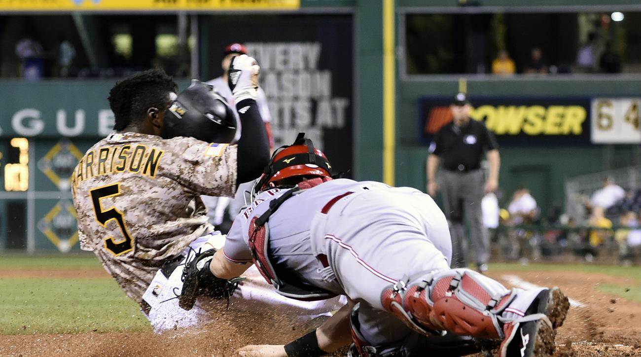 Pittsburgh Pirates' Josh Harrison slides safely into home past the tag of Cincinnati Reds' Tucker Barnhart during the sixth inning of a baseball game in Pittsburgh, Thursday, Sept. 8, 2016. (AP Photo/Fred Vuich)