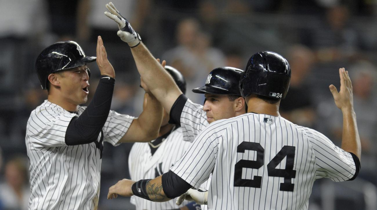 New York Yankees' Mark Teixeira celebrates with Gary Sanchez (24), Rob Refsnyder, left, and Starlin Castro, rear, after Teixeira hit a grand slam during the fourth inning of a baseball game against the Tampa Bay Rays Friday, Sept. 9, 2016, at Yankee Stadi
