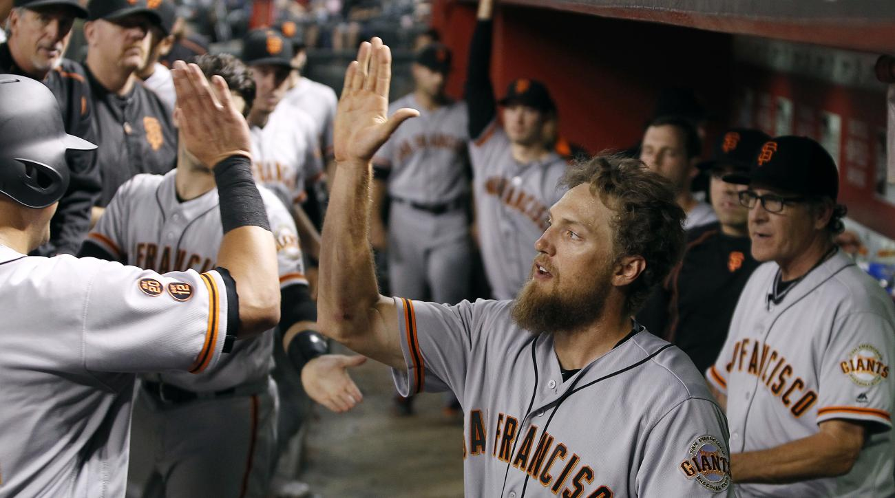 San Francisco Giants' Hunter Pence, center, congratulates Joe Panik, left, after Panik scored against the Arizona Diamondbacks during the seventh inning of a baseball game, Saturday, Sept. 10, 2016, in Phoenix. (AP Photo/Ralph Freso)