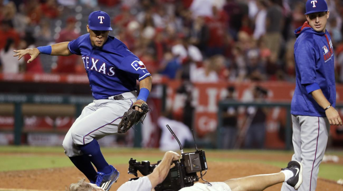Texas Rangers' Carlos Gomez, left, knocks over a cameraman while celebrating the team's 8-5 win against the Los Angeles Angels in a baseball game in Anaheim, Calif., Saturday, Sept. 10, 2016. (AP Photo/Chris Carlson)