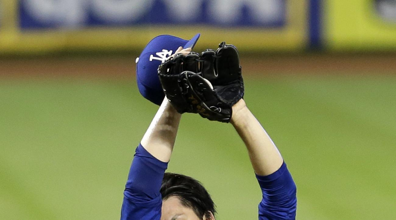 Los Angeles Dodgers' Kenta Maeda wipes his face after Miami Marlins' Derek Dietrich reached first base on an infield single that loaded the bases in the fourth inning of a baseball game, Sunday, Sept. 11, 2016, in Miami. (AP Photo/Alan Diaz)