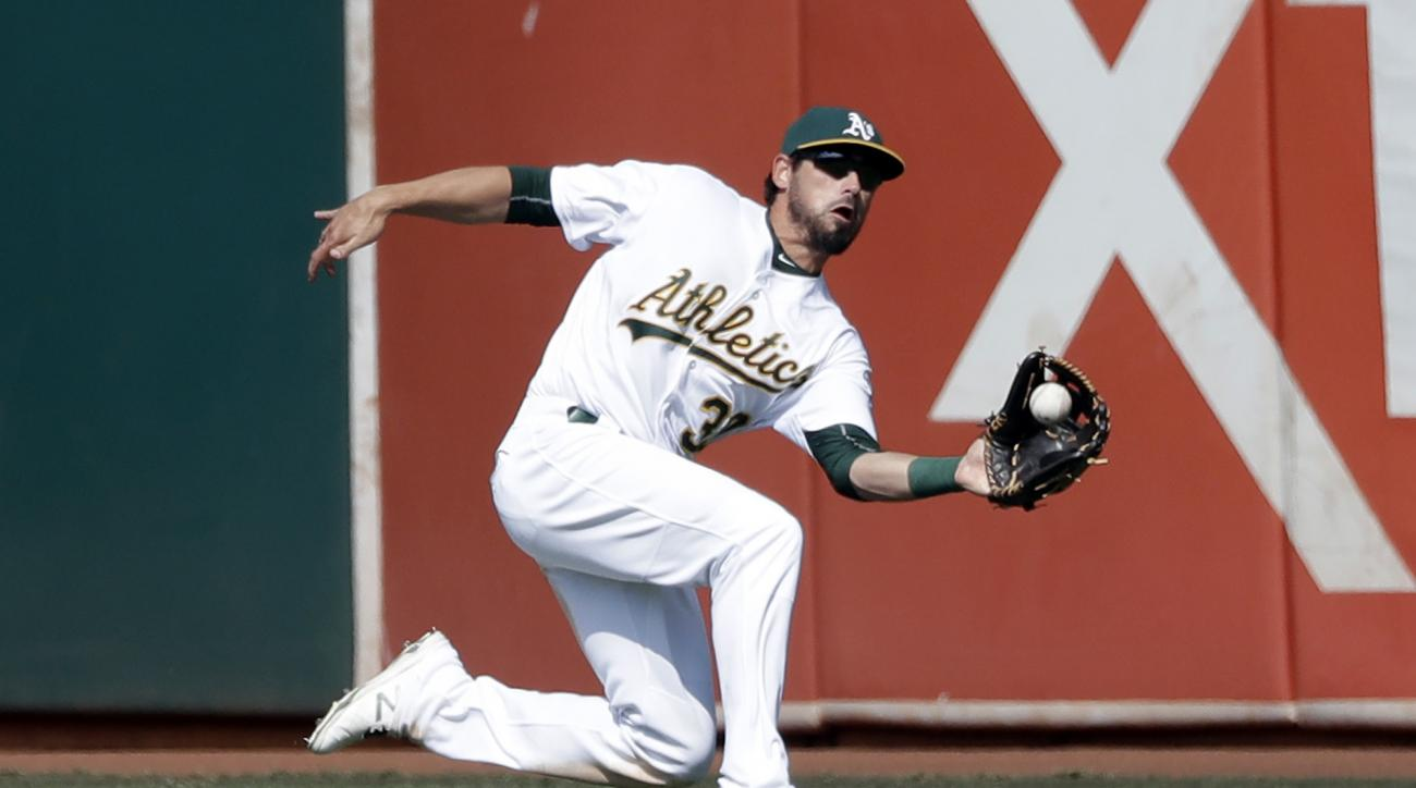 Oakland Athletics center fielder Brett Eibner makes a sliding catch on a fly ball from Seattle Mariners' Dae-Ho Lee during the eighth inning of a baseball game, Sunday, Sept. 11, 2016, in Oakland, Calif. (AP Photo/Marcio Jose Sanchez)