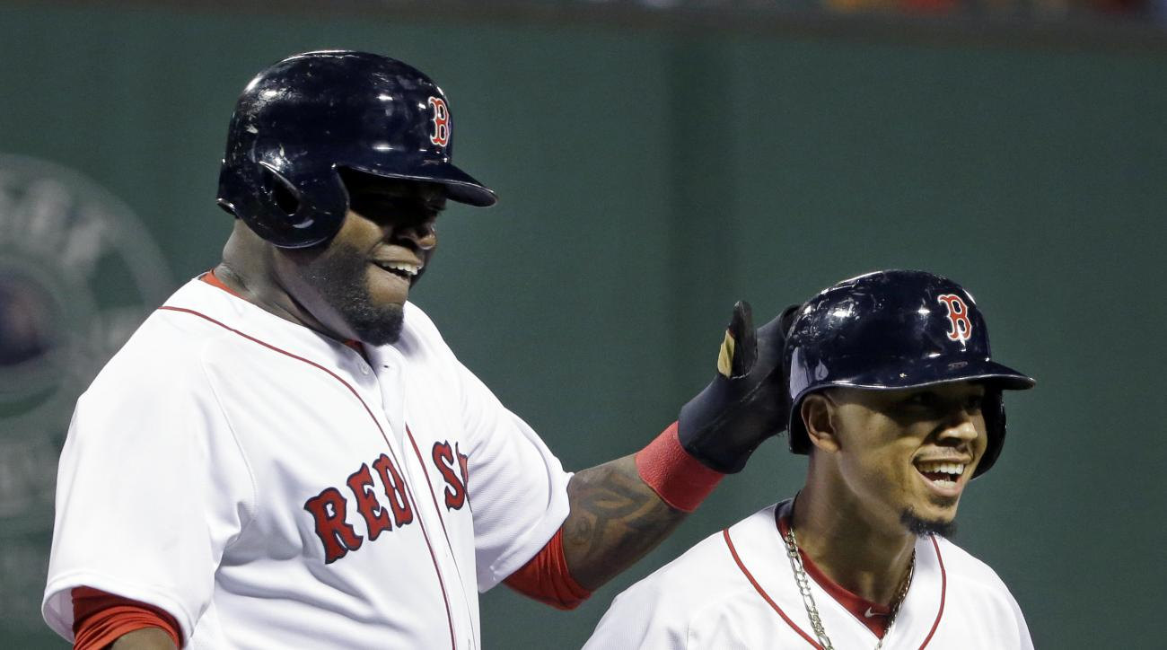 Boston Red Sox's David Ortiz, left, celebrates with Mookie Betts after they scored on a single by Hanley Ramirez in the first inning of a baseball game against the Baltimore Orioles at Fenway Park, Monday, Sept. 12, 2016, in Boston. (AP Photo/Elise Amendo