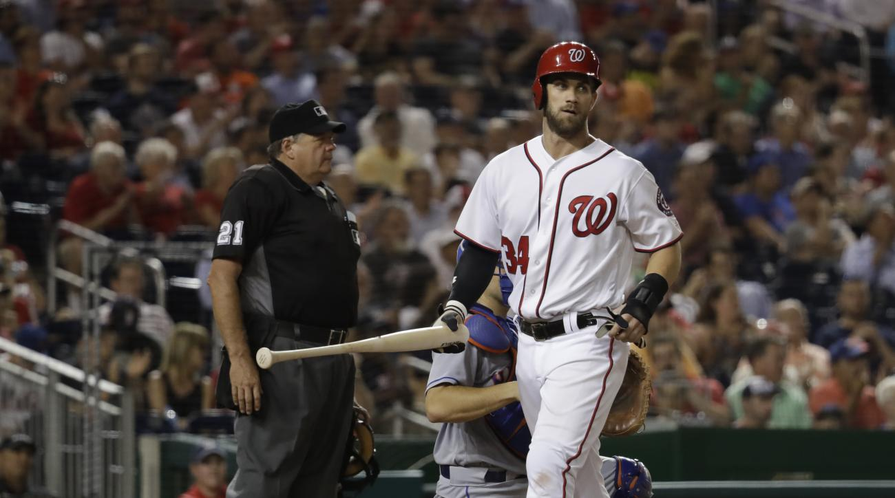 Washington Nationals' Bryce Harper (34) picks up the bat as he scores from a single by Ryan Zimmerman during the fourth inning of a baseball game against the New York Mets in Washington, Monday, Sept. 12, 2016. (AP Photo/Manuel Balce Ceneta)