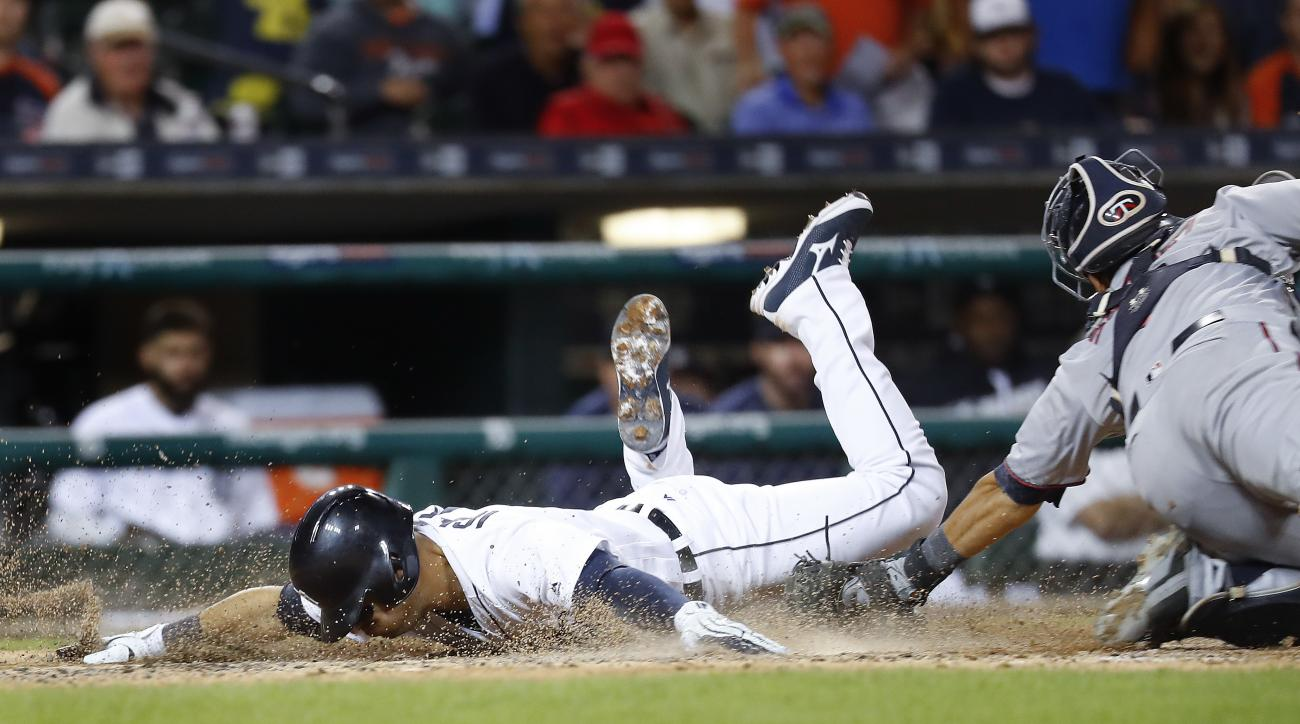 Detroit Tigers' Jose Iglesias (1) slides safely into home plate past the tag of Minnesota Twins catcher Kurt Suzuki on a Ian Kinsler sacrifice fly in the seventh inning during a baseball game in Detroit, Monday, Sept. 12, 2016. (AP Photo/Paul Sancya)