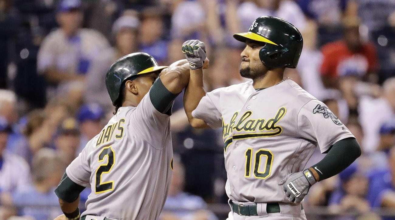 Oakland Athletics' Marcus Semien (10) celebrates with Khris Davis (2) after hitting a three-run home run during the sixth inning of a baseball game against the Kansas City Royals, Monday, Sept. 12, 2016, in Kansas City, Mo. (AP Photo/Charlie Riedel)