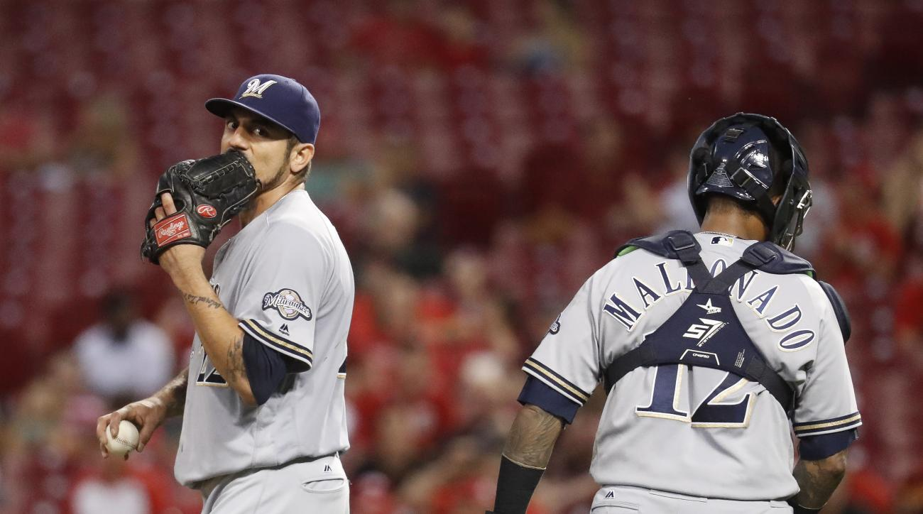 Milwaukee Brewers starting pitcher Matt Garza, left, meets with catcher Martin Maldonado during the third inning of a baseball game against the Cincinnati Reds, Tuesday, Sept. 13, 2016, in Cincinnati. (AP Photo/John Minchillo)