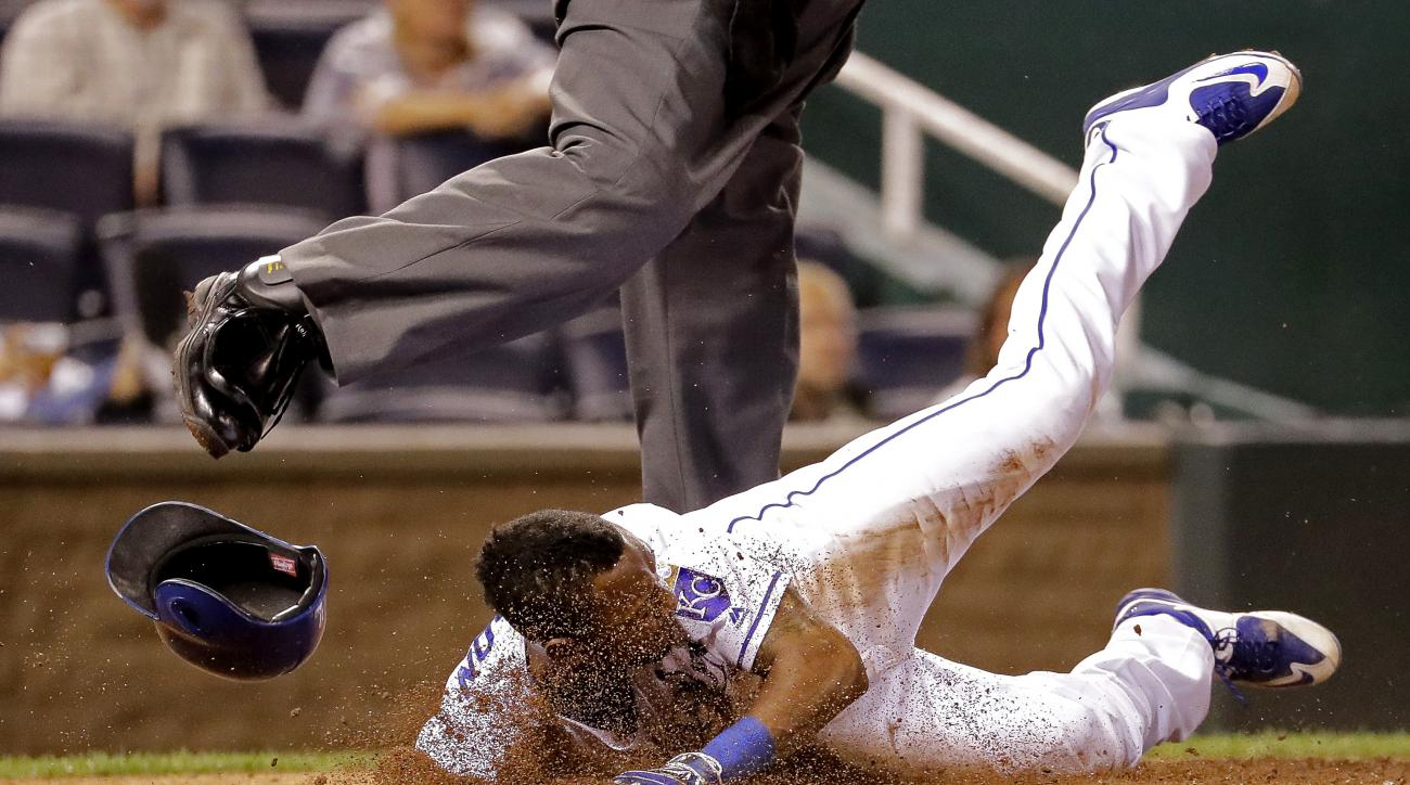 Kansas City Royals' Jarrod Dyson slides under home plate umpire Dana DeMuth after he was tagged out during the seventh inning of a baseball game against the Oakland Athletics Tuesday, Sept. 13, 2016, in Kansas City, Mo. (AP Photo/Charlie Riedel)