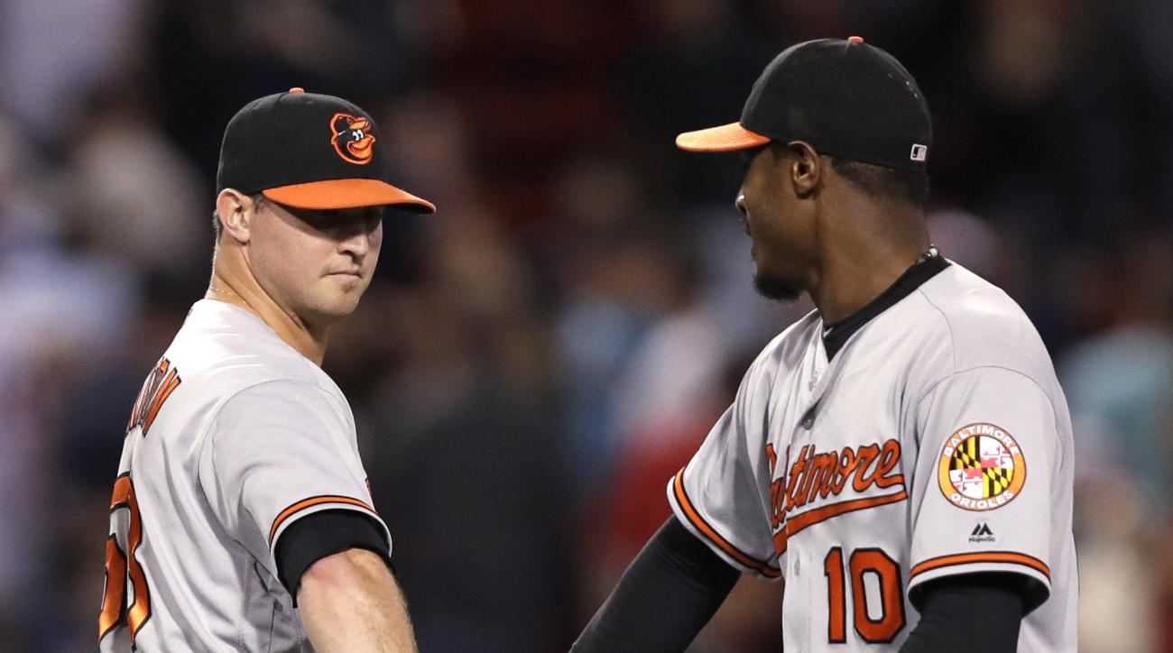 Baltimore Orioles pitcher Zach Britton, left, is congratulated by outfielder Adam Jones after defeating the Boston Red Sox 6-3 in a baseball game at Fenway Park, Tuesday, Sept. 13, 2016, in Boston. (AP Photo/Charles Krupa)