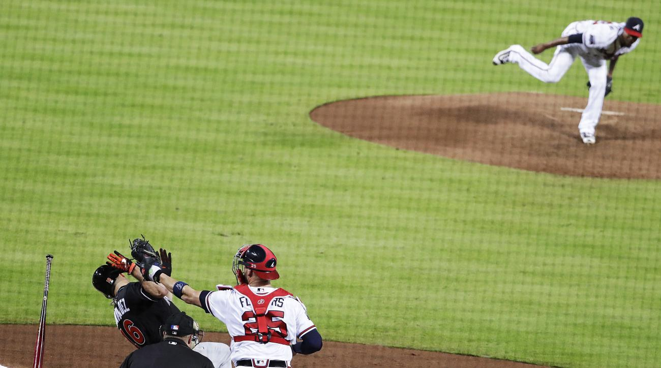 Miami Marlins' Jose Fernandez, left, falls to the ground to get out of the way of a high pitch by Atlanta Braves' starting pitcher Julio Teheran, top right, during the fifth inning of a baseball game in Atlanta, Wednesday, Sept. 14, 2016. (AP Photo/David