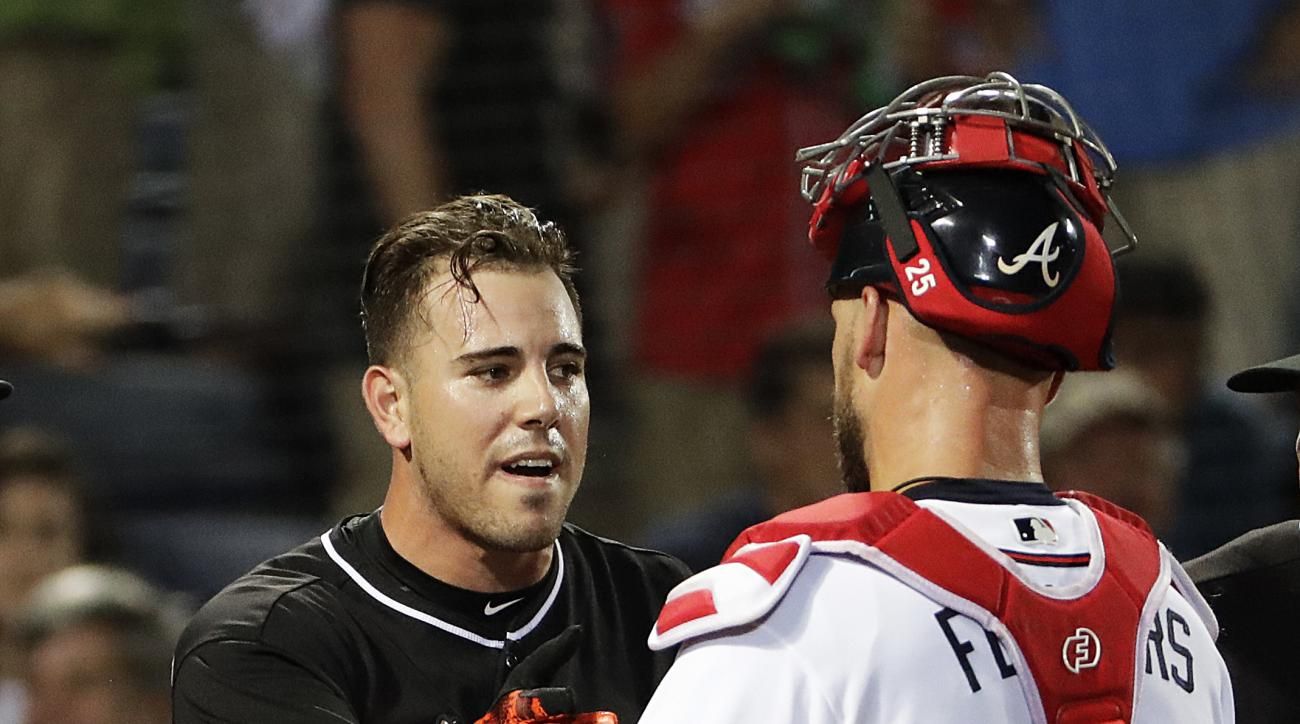 Miami Marlins' Jose Fernandez, left, talks with Atlanta Braves catcher Tyler Flowers after Atlanta reliever Jose Ramirez threw inside to Fernandez during the seventh inning of a baseball game in Atlanta, Wednesday, Sept. 14, 2016. The benches for both tea