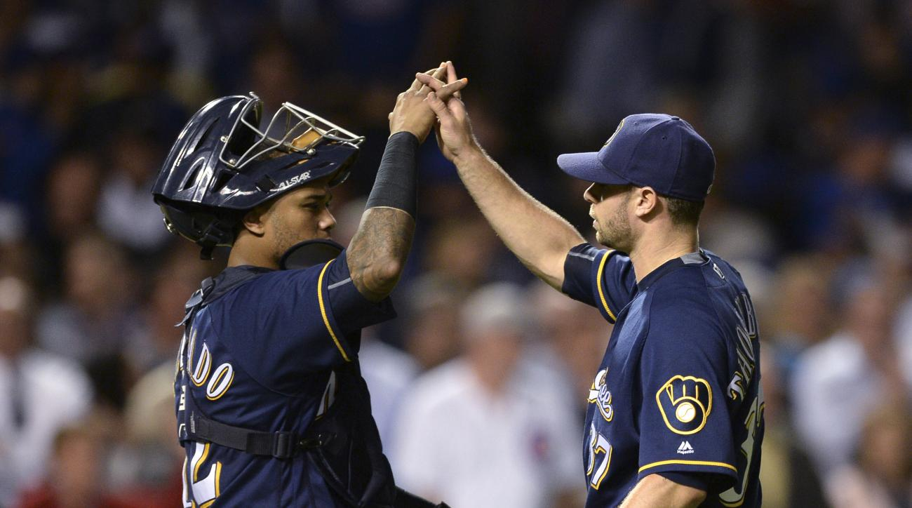 Milwaukee Brewers closing pitcher Tyler Thornburg right, celebrates with catcher Martin Maldonado left, after the Brewers defeated the Chicago Cubs 5-4 in a baseball game Thursday, Sept. 15, 2016, in Chicago. (AP Photo/Paul Beaty)