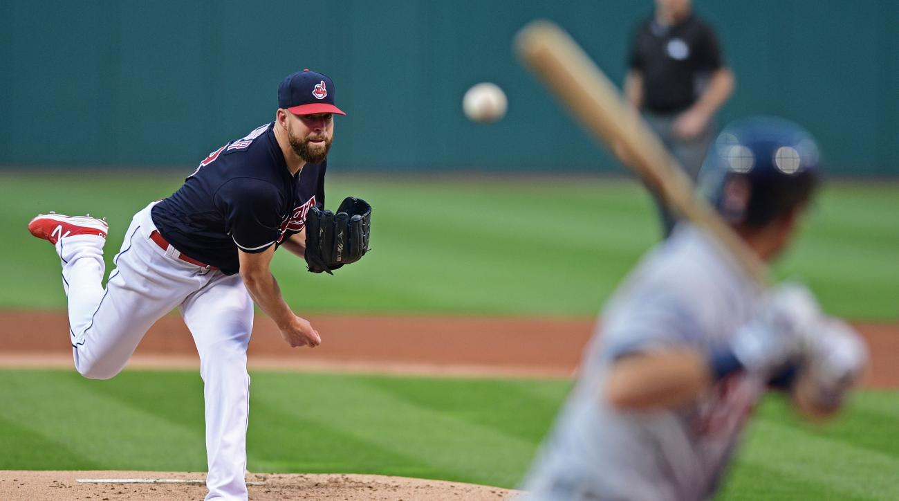 Cleveland Indians starting pitcher Corey Kluber, left, delivers in the first inning of a baseball game against the Detroit Tigers, Friday, Sept. 16, 2016, in Cleveland. (AP Photo/David Dermer)