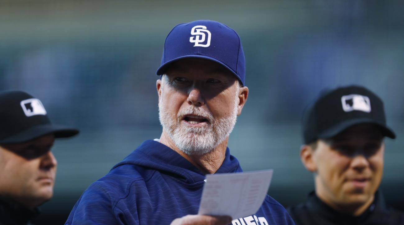 San Diego Padres bench coach Mark McGwire hands the lineup to umpires before facing the Colorado Rockies in the first inning of a baseball game Friday, Sept. 16, 2016, in Denver. (AP Photo/David Zalubowski)