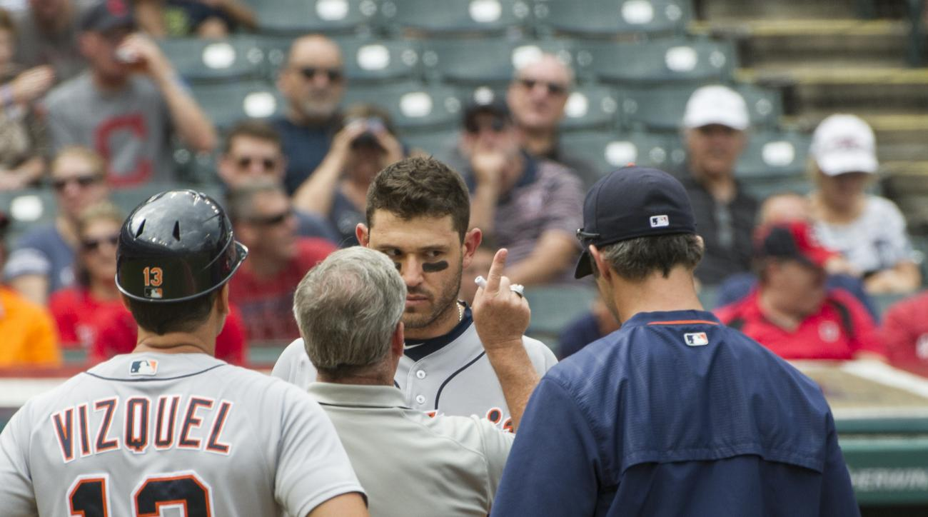 Detroit Tigers' Ian Kinsler is checked by a trainer after being hit in the head by Cleveland Indians starting pitcher Trevor Bauer during the third inning of a baseball game in Cleveland, Sunday, Sept. 18, 2016. Tigers coach Omar Vizquel (13) and manager