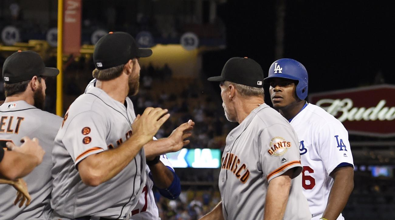 San Francisco Giants starting pitcher Madison Bumgarner, second from left, and Los Angeles Dodgers' Yasiel Puig, right, argue as first base coach Bill Hayes stands between them during a scuffle that emptied both benches after Puig was thrown out at first